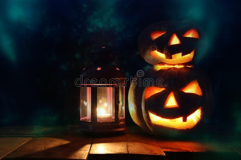 Halloween Pumpkins on wooden table in front of spooky dark background. Jack o lantern royalty free stock images