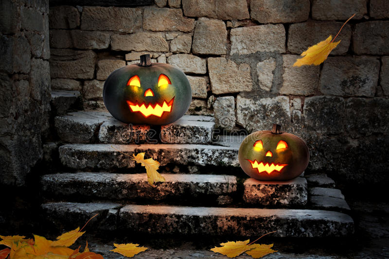 Halloween pumpkins in the yard of an old house at night. In the bright moonlight royalty free stock photography