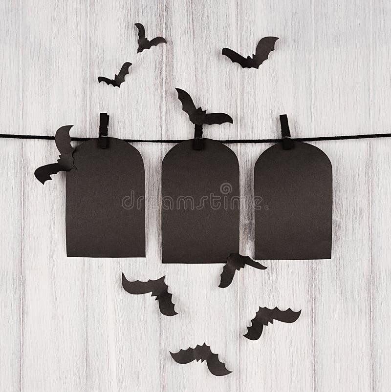 Halloween-reclamespot omhoog De lege zwarte verkoop etiketteert graf het hangen op wasknijpers, troepknuppels en witte houten pla royalty-vrije stock afbeeldingen