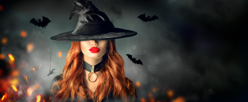 Halloween Reizvolles Hexeportrait Schönheit im Hexenhut mit dem langen gelockten roten Haar stockfotos