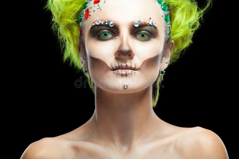 Halloween Retrato da menina bonita nova com o esqueleto da composição em sua cara E cabelo verde Isolado no preto fotos de stock