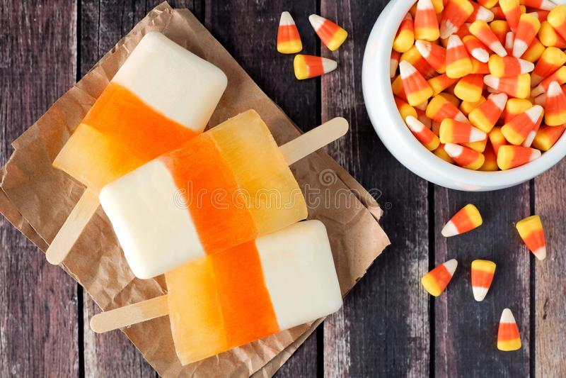 Halloween-Süßigkeitsmaiseis am stiel auf rustikalem hölzernem Hintergrund lizenzfreies stockfoto