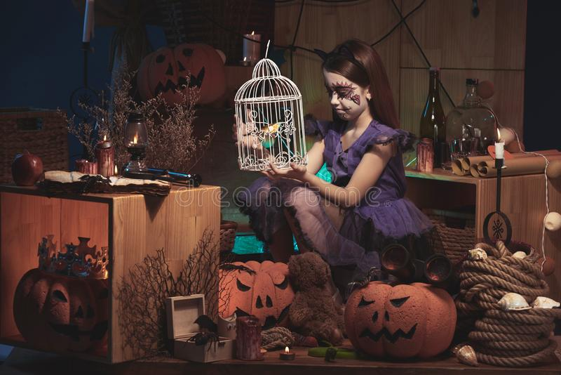 Halloween. Sad girl in Halloween costume looking at bird in cage stock photo