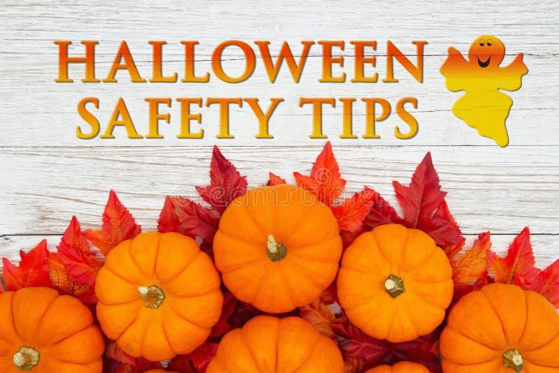 Halloween Safety Tips-Nachricht mit roten und orangefarbenen Fallblättern und Kürbis auf verwittertem Holz lizenzfreies stockbild