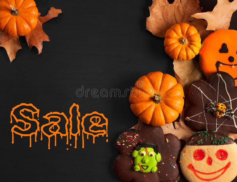 Funny halloween gingerbread cookies on black wooden table. Halloween sale stock images