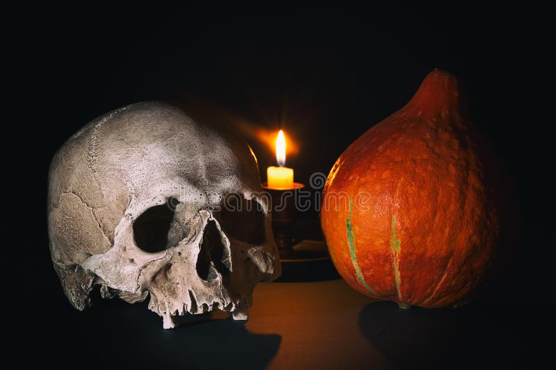Halloween scene. Human skull near Halloween pumpkin with burning candle on dark black background. Close up image royalty free stock photos
