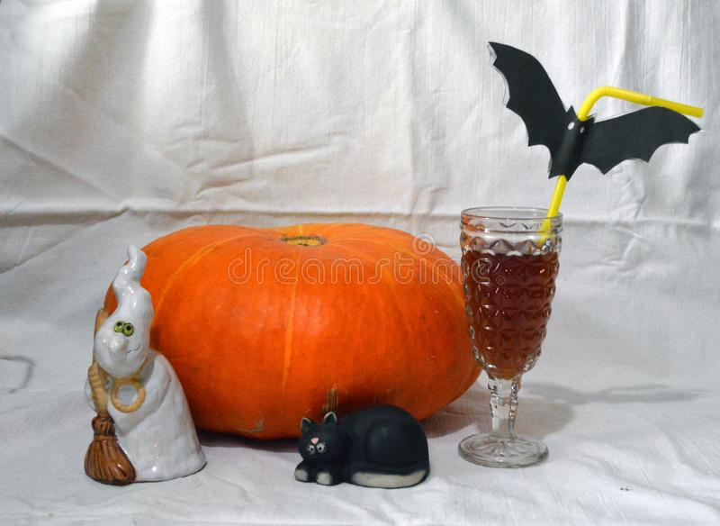 Halloween scenery with a ghost, a black cat, a pumpkin and a glass stock image