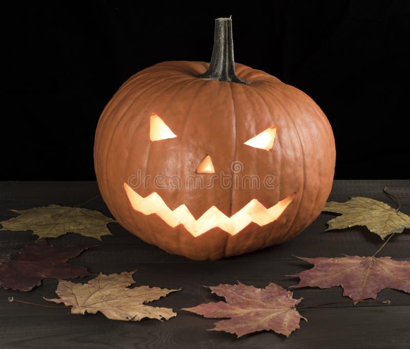 Halloween schnitzte Kürbis, Steckfassung-Olaterne auf Holztisch mit Blättern lizenzfreie stockfotos