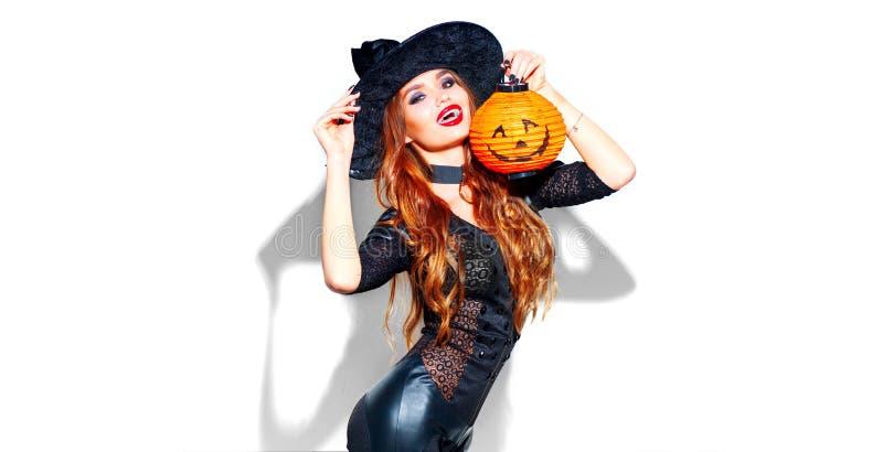halloween Sexig häxa med ljus feriemakeup Härlig ung kvinna som poserar i häxadräkt med pumpalyktan royaltyfri fotografi