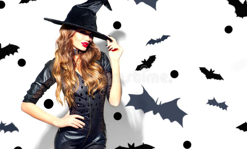 Halloween Sexy Girl wearing witch costume with a hat. Party, Celebrating. Beauty Woman with long hair and holiday bright makeup stock photos