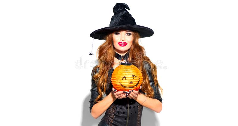 Halloween Sexy Girl wearing witch costume with a hat with pumpkin lantern, showing product. Sales, Party, Celebrating. Beauty surprised Woman isolated on white royalty free stock image