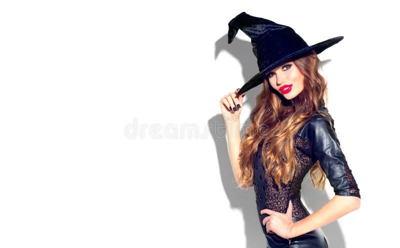 Halloween Sexy Hexe mit hellem Feiertagsmake-up Schöne junge Frau, die im Hexenkostüm über Weiß aufwirft stockfotografie