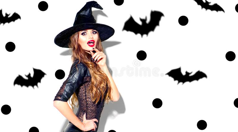 Halloween. witch with bright holiday makeup. Beautiful surprised young woman posing in witches costume stock images