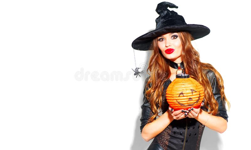 Halloween. witch with bright holiday makeup. Beautiful young woman posing in witches costume with pumpkin lantern royalty free stock image