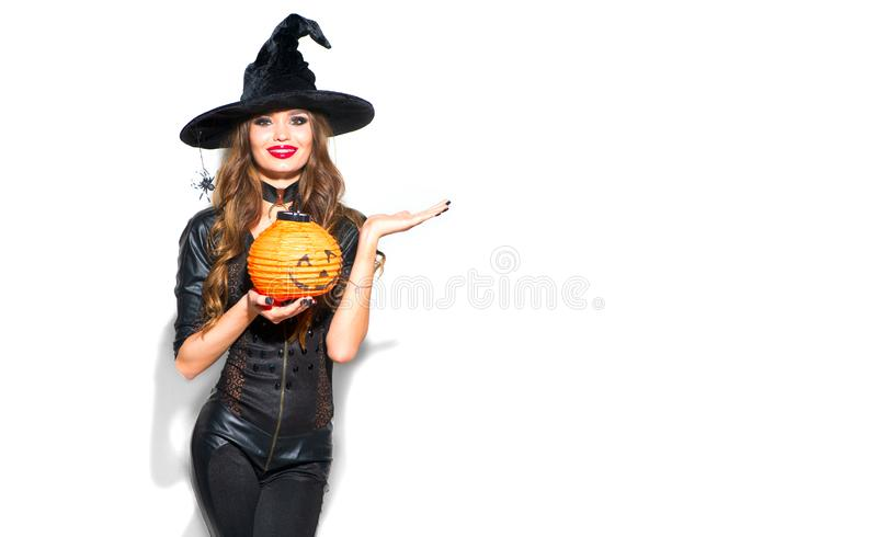 Halloween. witch with bright holiday makeup. Beautiful young woman in witches costume with pumpkin lantern pointing hand stock photo