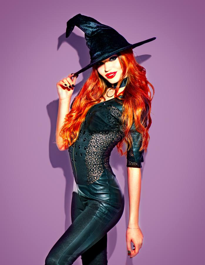 Halloween. witch with bright makeup and long red hair. Beautiful young woman posing in witches costume. Over violet background stock photo