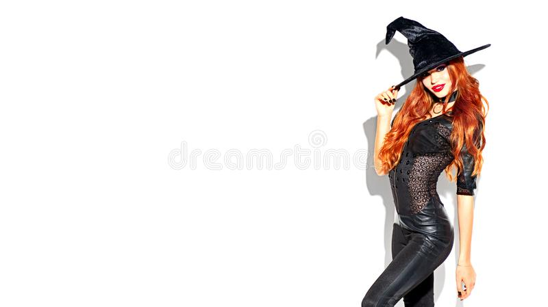 Halloween. witch with bright makeup and long red hair. Beautiful young woman posing in witches costume. Over white background stock photo
