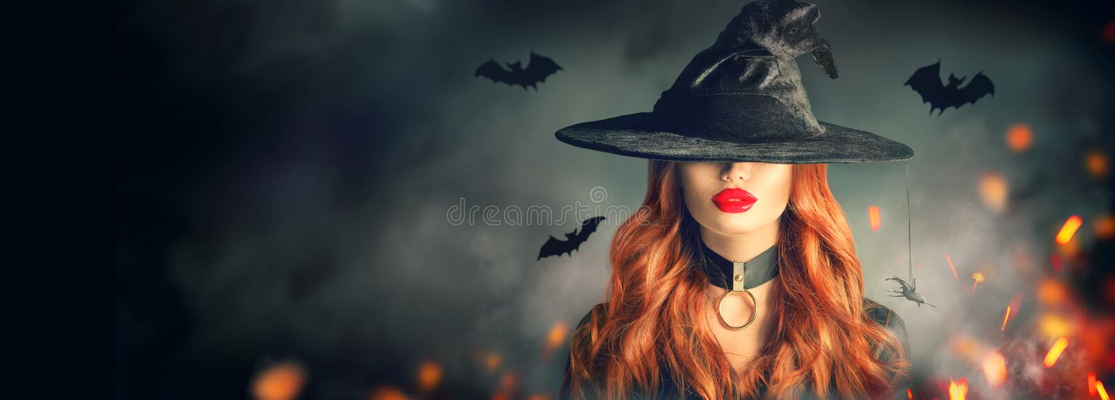 Halloween. witch portrait. Beautiful young woman in witches hat with long curly red hair over spooky dark magic forest royalty free stock photo