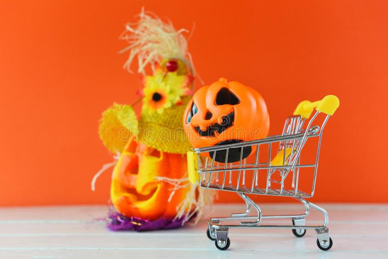 Halloween shopping holiday concept - accessories with pumpkin jack o lantern in a shopping cart on orange background. Halloween shopping holiday concept / stock photography