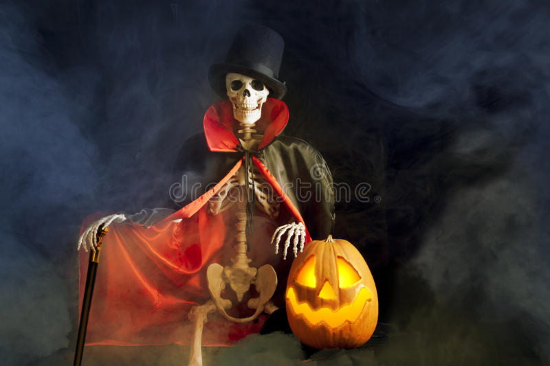 Halloween Skeleton and Jack-O-Lantern. A dapper Halloween skeleton walking through mist, while dressed in red and black silk cape, top hat and walking cane with royalty free stock photos