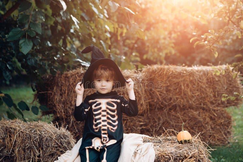 Halloween skeleton kid. Boy sitting on the haystack. Happy day. Little child enjoy walk. Happy laughing child in costume stock photo
