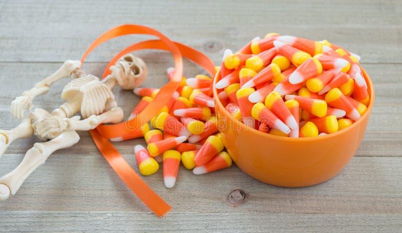 Halloween-Skelett, Satinband und eine orange Schüssel, die mit Süßigkeitsmais auf einem hölzernen Hintergrund überläuft stockbild