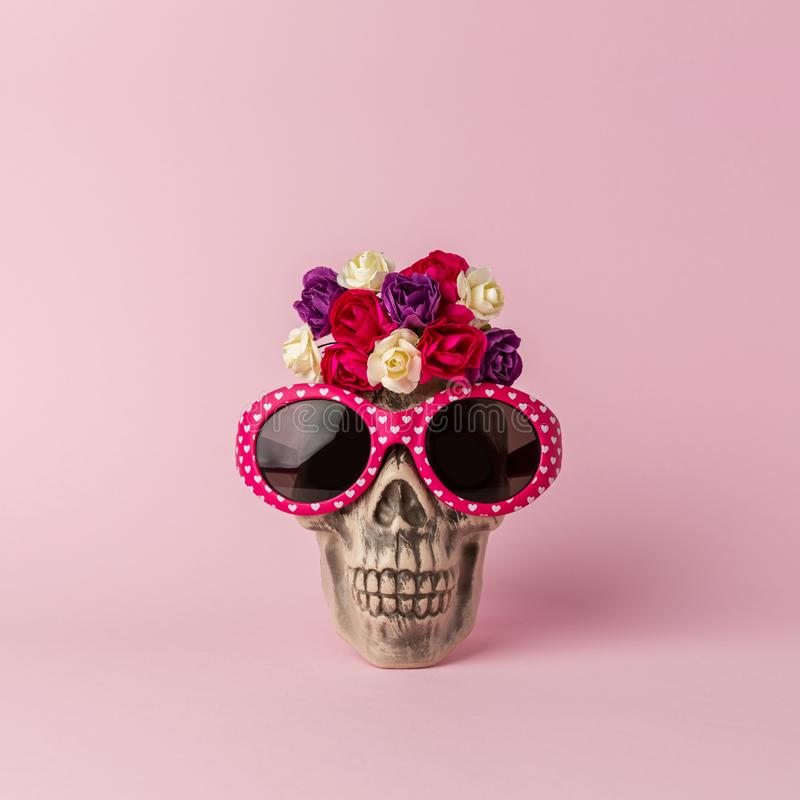 Halloween skull head with flowers and sunglasses on pink background. Minimal holiday concept royalty free stock image