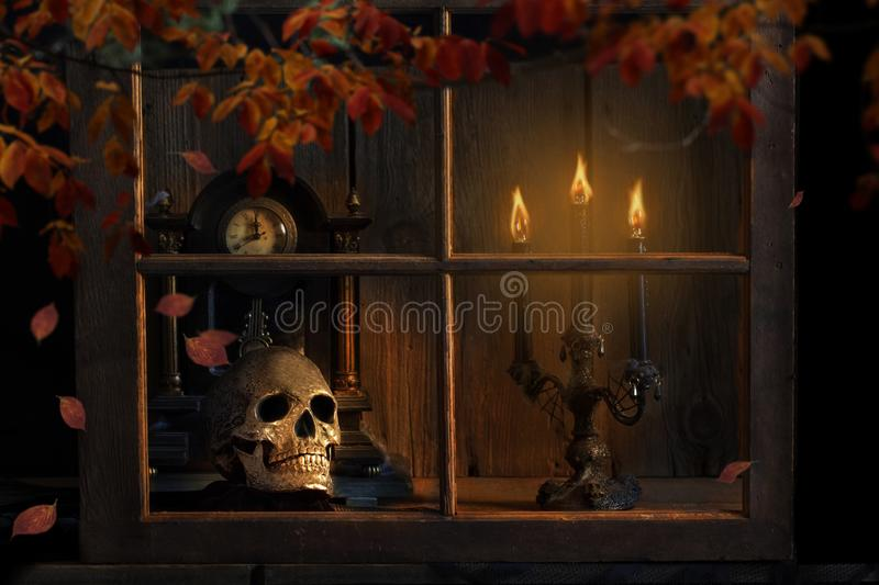 Halloween Skull Looking Out Window. Silver metal human skull looking out window onto dark fall night, candelabra casting warm glow, and old clock about to strike stock photos