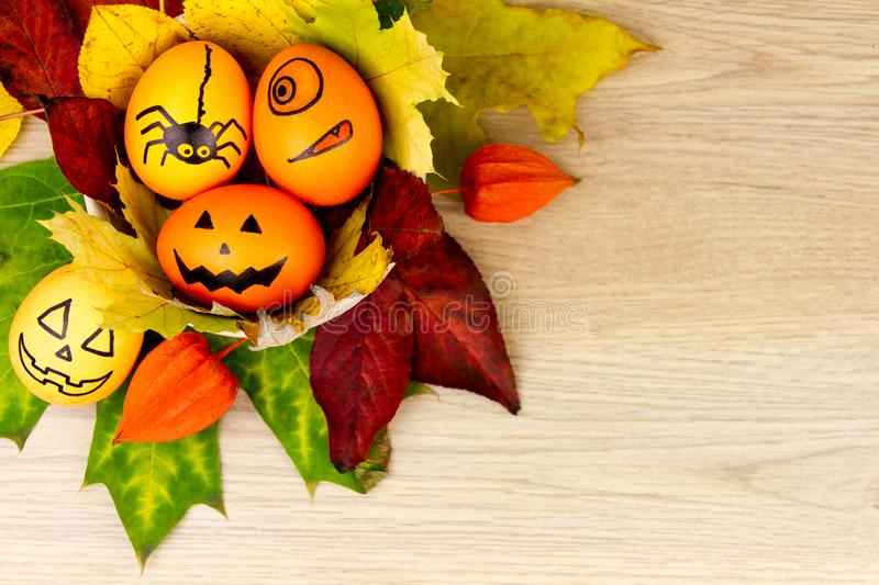 Halloween small spooky pumpkins. Halloween small spooky eggs with faces and spider and orange yellow autumn leafs as decoration for holiday on wooden background royalty free stock image