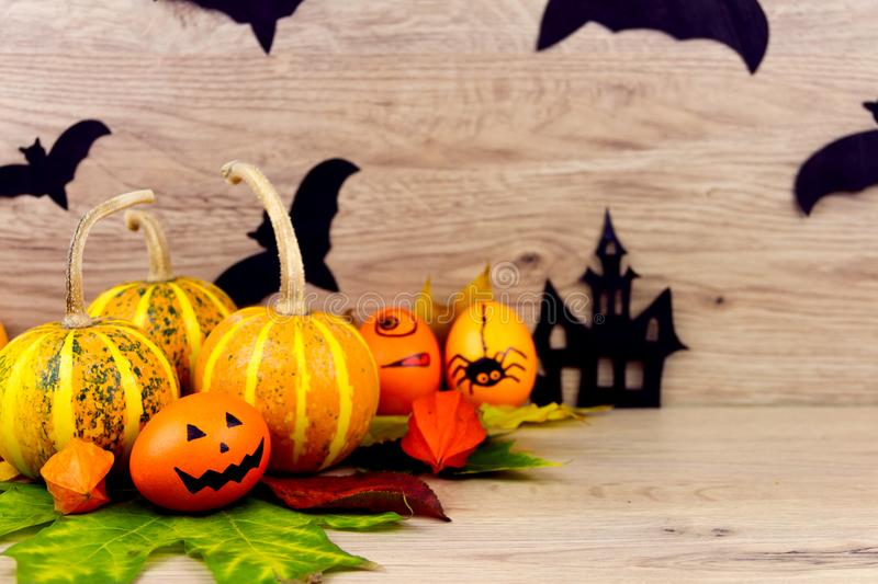 Halloween small spooky pumpkins. And eggs with faces orange yellow autumn leafs and scary black bats as decoration for holiday on wooden background royalty free stock photo
