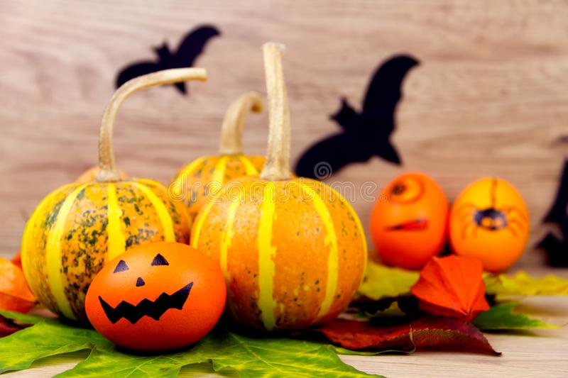 Halloween small spooky pumpkins. And eggs with faces orange yellow autumn leafs and scary black bats as decoration for holiday on wooden background royalty free stock photography