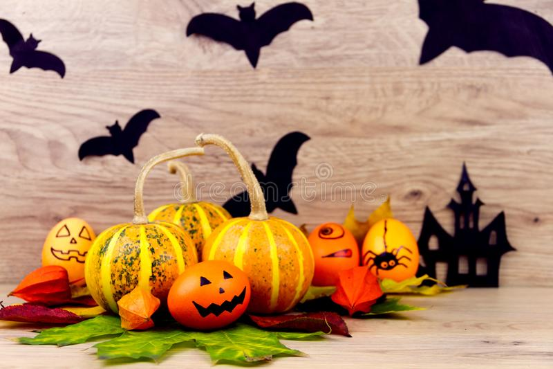 Halloween small spooky pumpkins. And eggs with faces orange yellow autumn leafs and scary black bats as decoration for holiday on wooden background royalty free stock photos