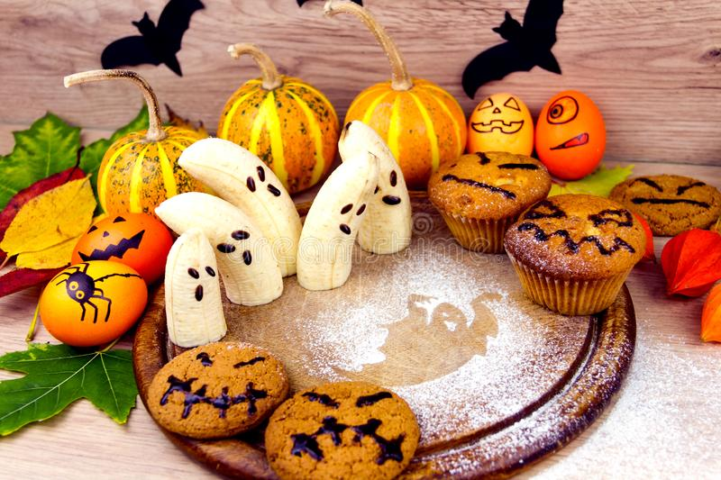 Halloween small spooky pumpkins sweet cookies bananas with faces. Orange yellow autumn leafs and scary black bats as decoration for holiday on wooden background royalty free stock photos