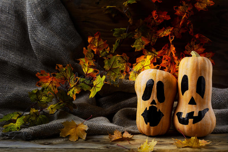 Halloween smiling butternut squash on dark rustic background. Halloween symbol jack-o-lantern background royalty free stock photos