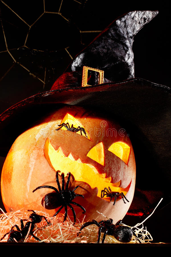 Halloween sorcery. Image of Halloween pumpkin in hat with spiders on it royalty free stock images