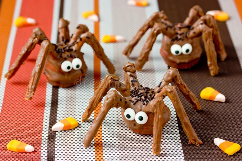 Halloween spider cakes with candy eyes in chocolate, Halloween treats stock photography