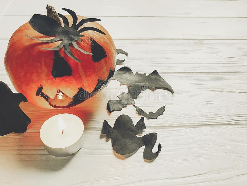 halloween. spooky jack lantern pumpkin with ghost bats and spider black decorations in light on white wooden background. holiday stock photo