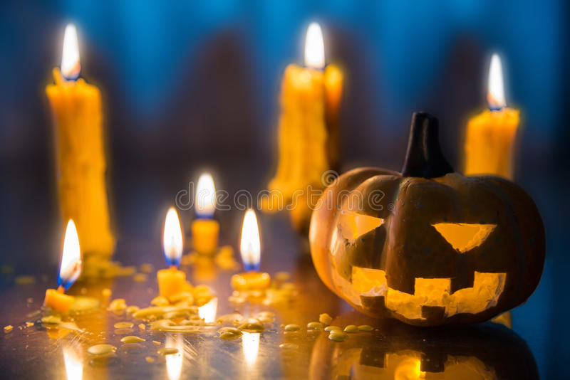 Halloween spooky Jack-O-Lantern pumpkin head with candles decoration at night background, selective focus royalty free stock image