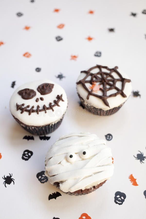 Halloween spooky muffin cupcakes. Home made Halloween spooky and creepy muffin cupcakes as a mummies, spider net and horror pumpkin, decorated with chocolate to stock photo