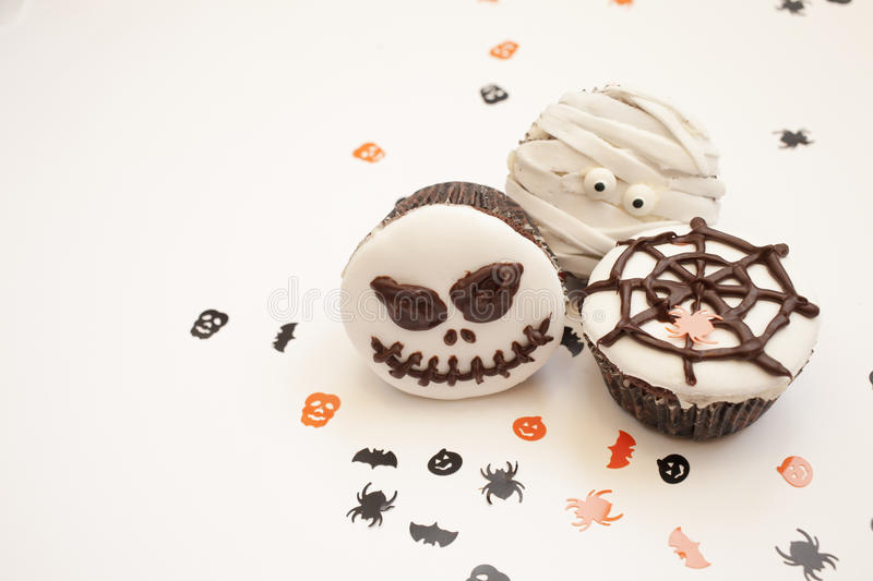 Halloween spooky muffin cupcakes. Home made Halloween spooky and creepy muffin cupcakes as a mummies, spider net and horror pumpkin, decorated with chocolate to royalty free stock images