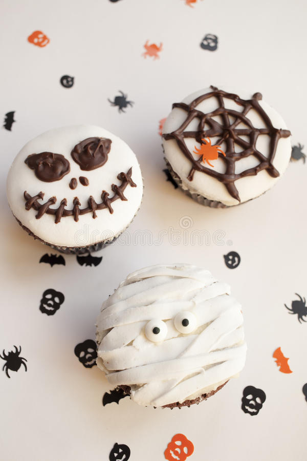 Halloween spooky muffin cupcakes. Home made Halloween spooky and creepy muffin cupcakes as a mummies, spider net and horror pumpkin, decorated with chocolate to royalty free stock photography