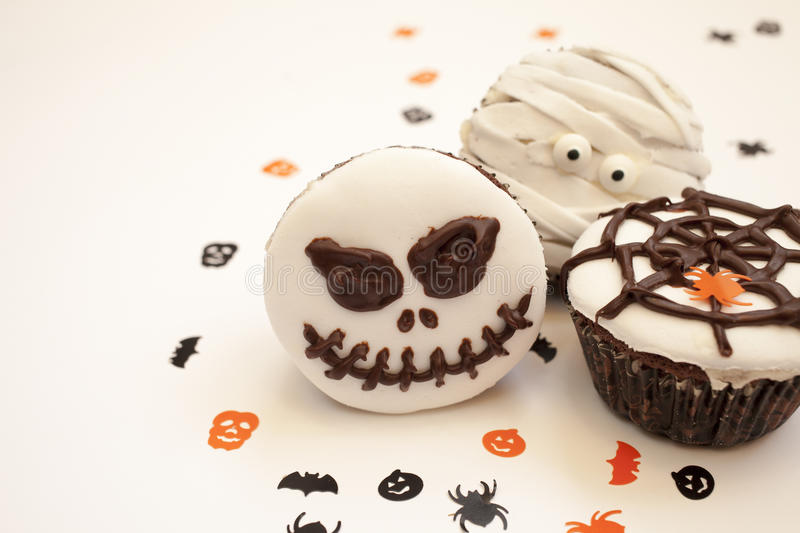 Halloween spooky muffin cupcakes. Home made Halloween spooky and creepy muffin cupcakes as a mummies, spider net and horror pumpkin, decorated with chocolate to stock photos