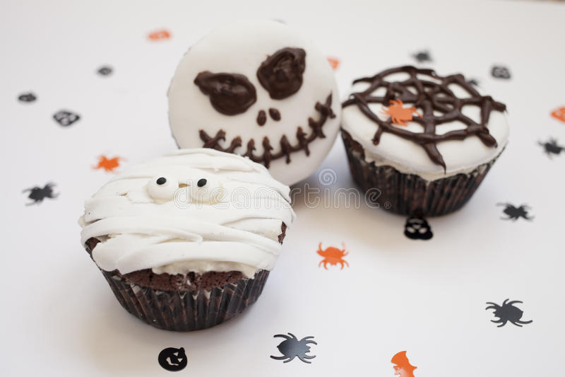 Halloween spooky muffin cupcakes. Home made Halloween spooky and creepy muffin cupcakes as a mummies, spider net and horror pumpkin, decorated with chocolate to stock image