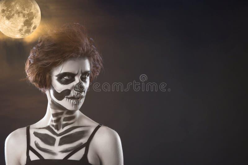 halloween Stående av den unga härliga flickan med sminkskelettet på hennes framsida royaltyfri bild