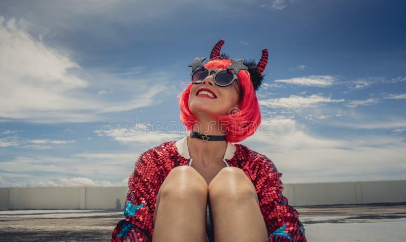 halloween Stående av en härlig flicka i en röd peruk med hornnärbild mot en blå himmel Sitta på foofen Rött fotografering för bildbyråer
