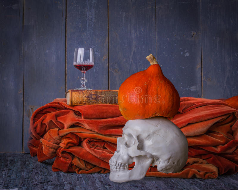 Halloween still life with skull, book, pumpkin and red wine royalty free stock photos