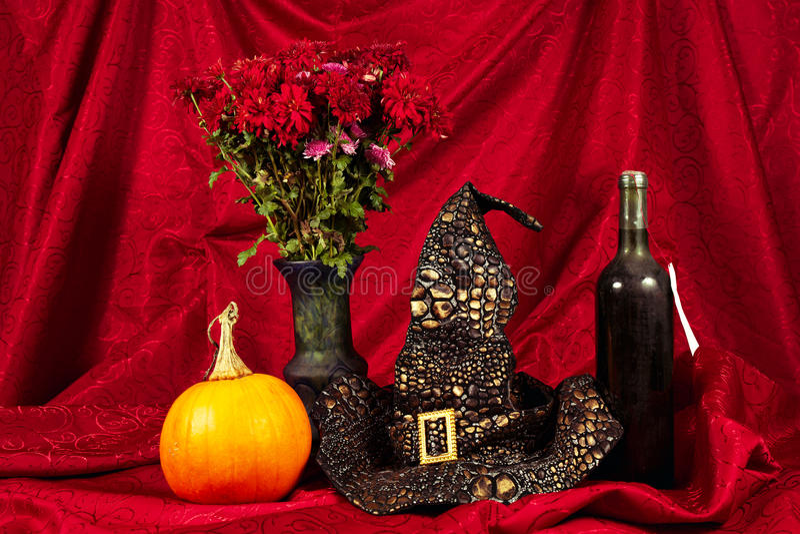 Halloween-stilleven met pompoen, wijn, met hoed en bloemen royalty-vrije stock afbeeldingen