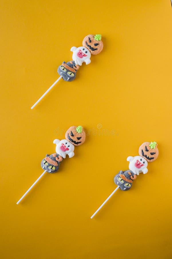 Halloween-suikergoed in een afwisselend patroon op een kleur wordt geschikt die stock afbeeldingen