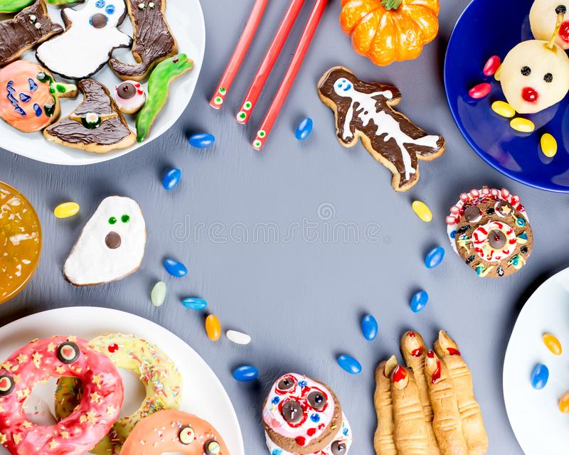 Halloween sweet treats, party food concept. Scary cookies, monster biscuits and fruits on grey background. royalty free stock photos