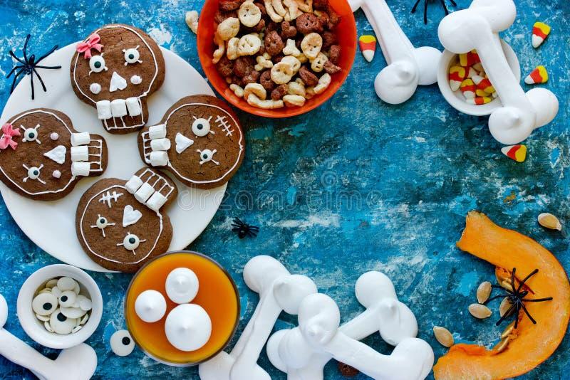 Halloween sweets and treats. Skull cookies, candy corn, pumpkin panna cotta, meringue bones top view royalty free stock photography